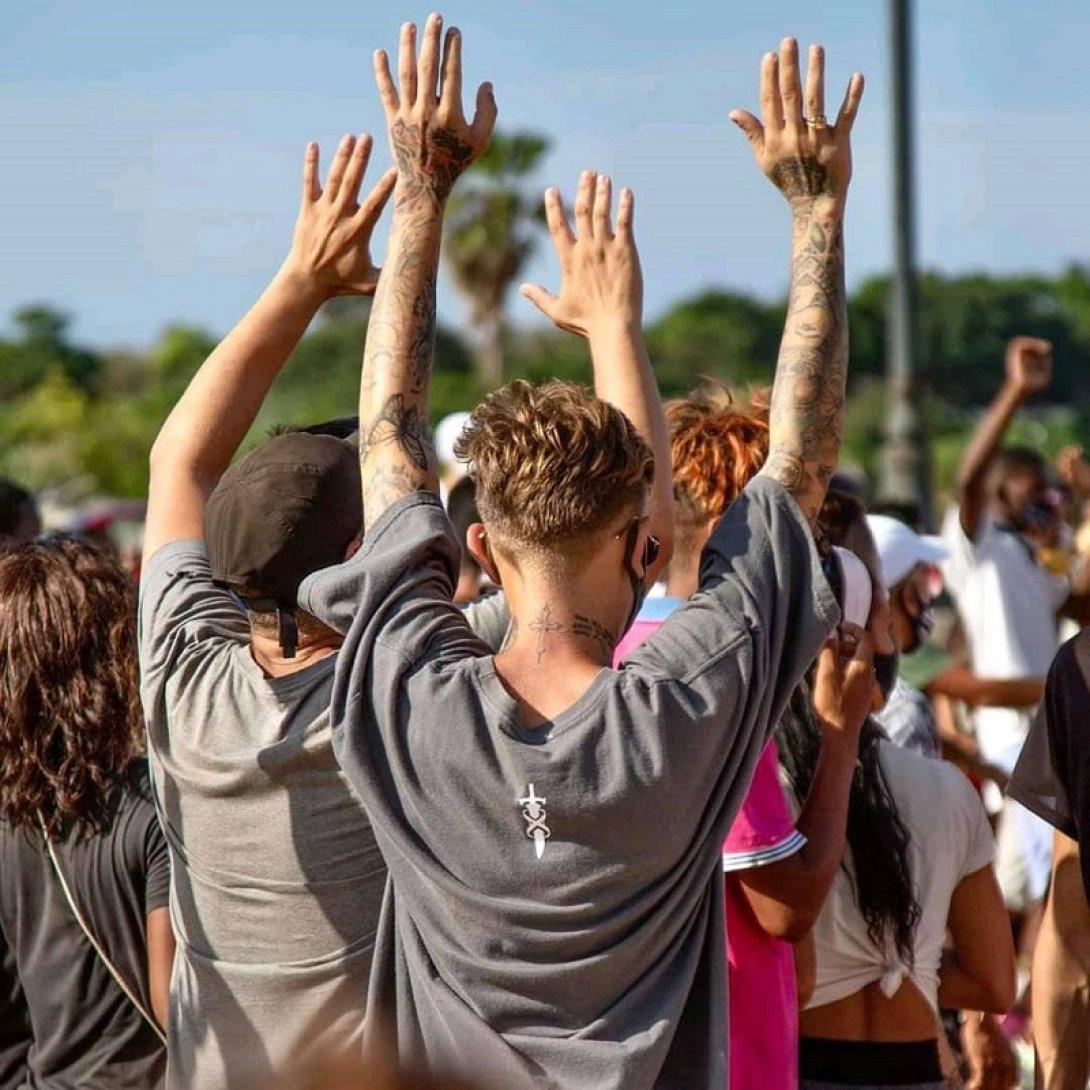 Jóvenes manifestantes cubanos con brazos levantados ante los represores.